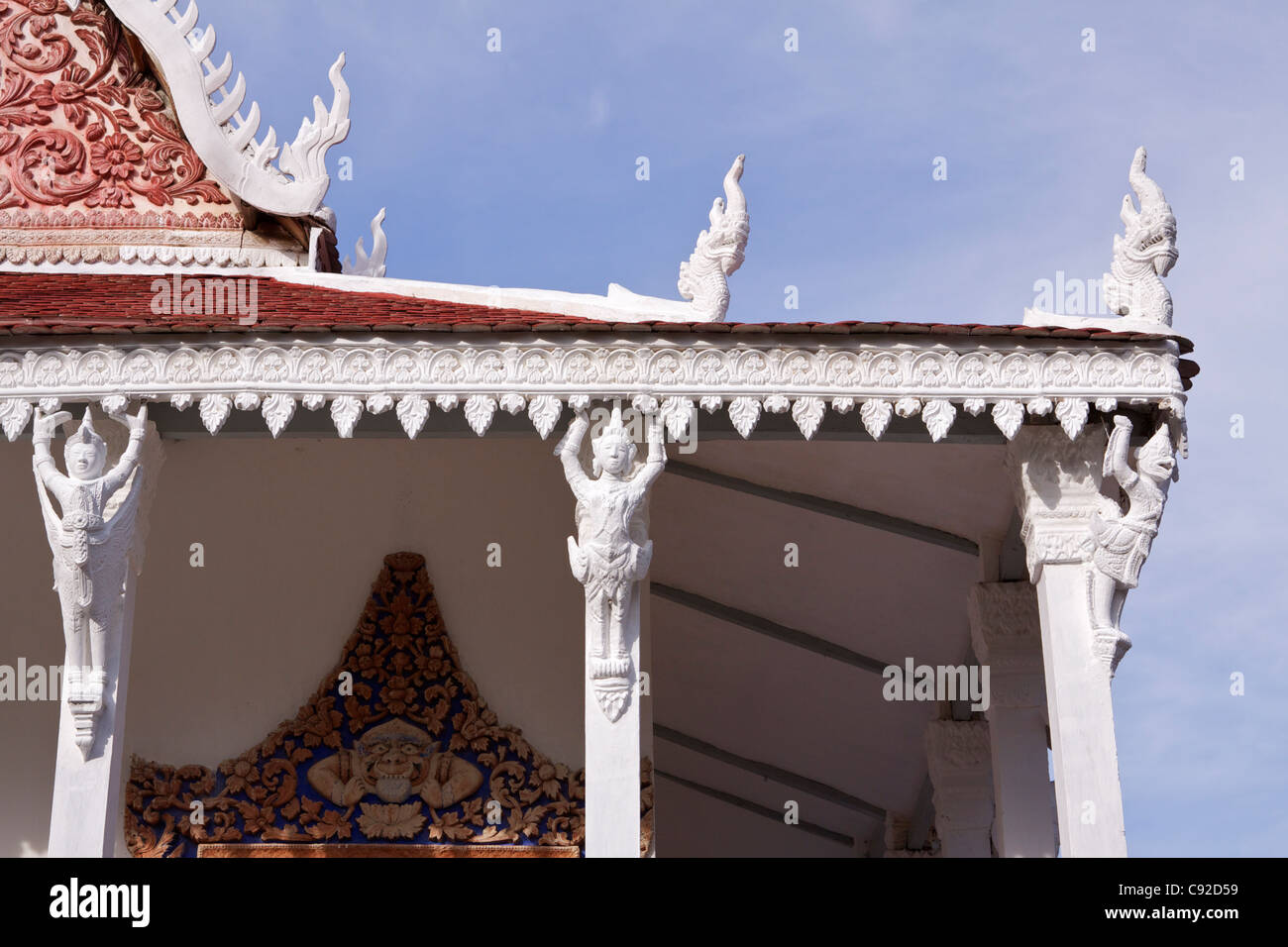 The ornate white mouldings and carvings on the red tiled roof of the original Wat Kampong Tralach Vihara have been - Stock Image