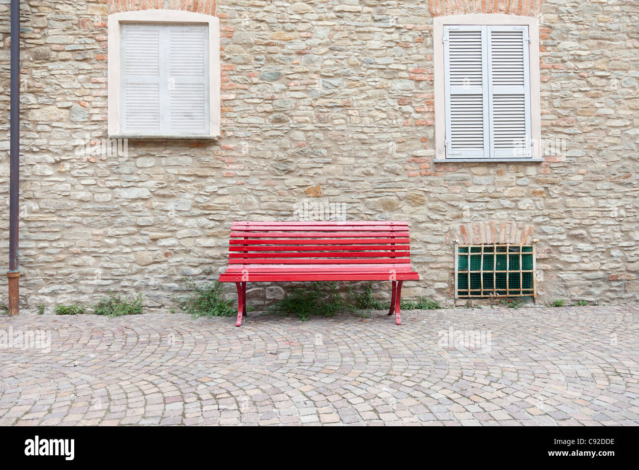 Red bench on cobbled village street - Stock Image