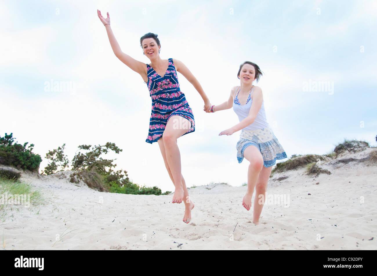 Woman and girl running on beach Stock Photo