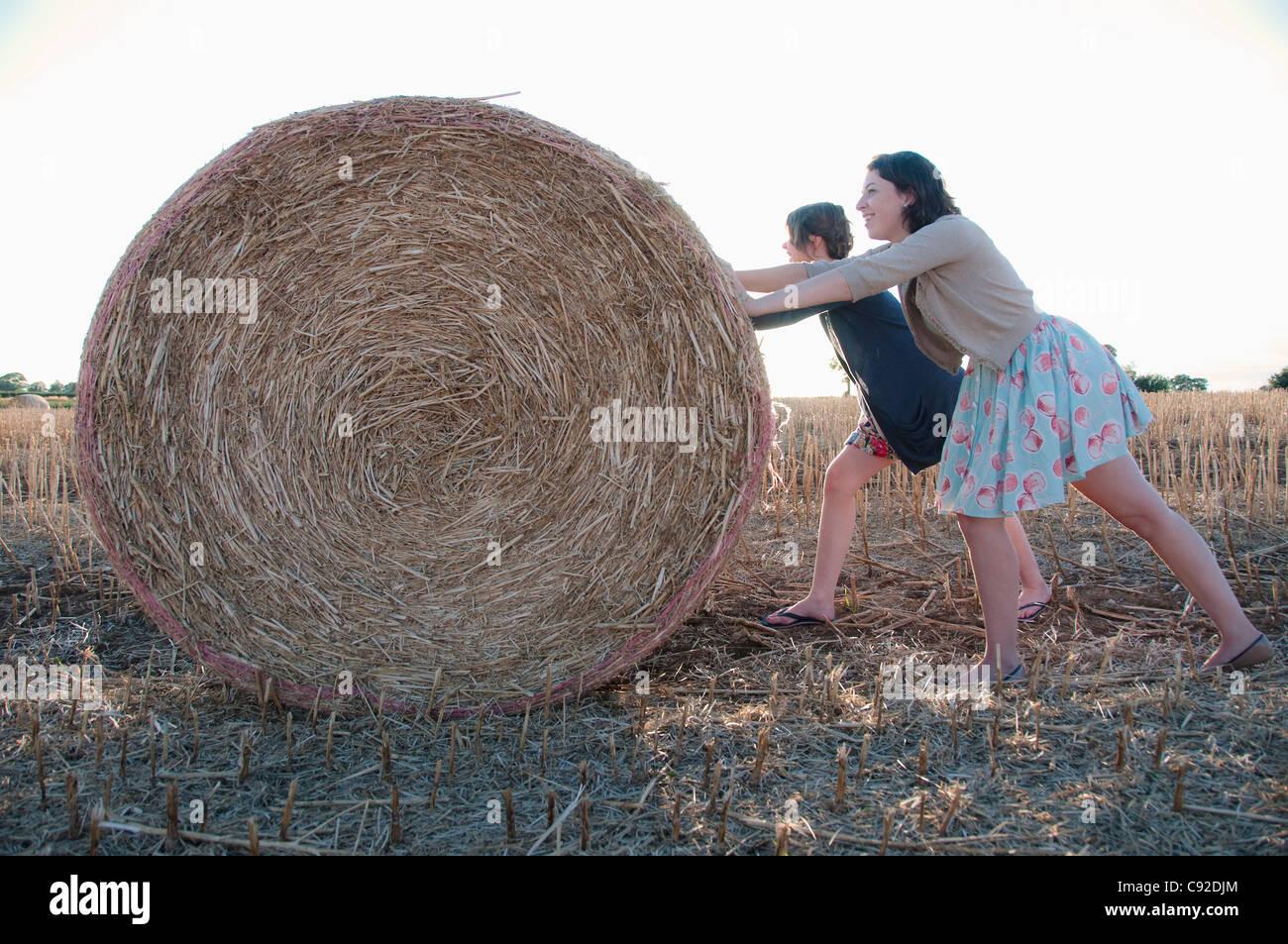 Girls pushing hay bale in field - Stock Image