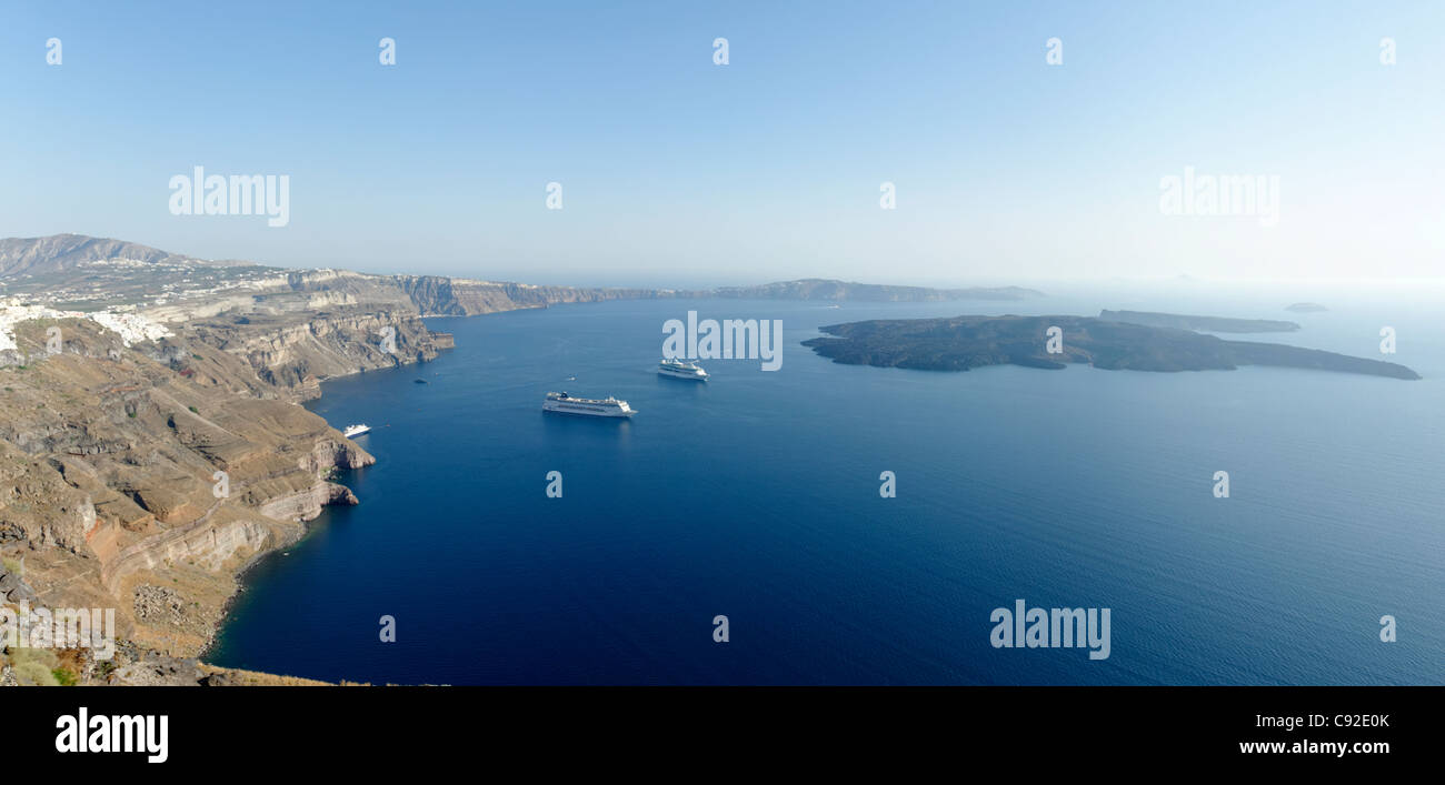 Panoramic view of the vast Santorini Caldera with cruise ships in its blue sea. To the left is the whitewashed capital - Stock Image
