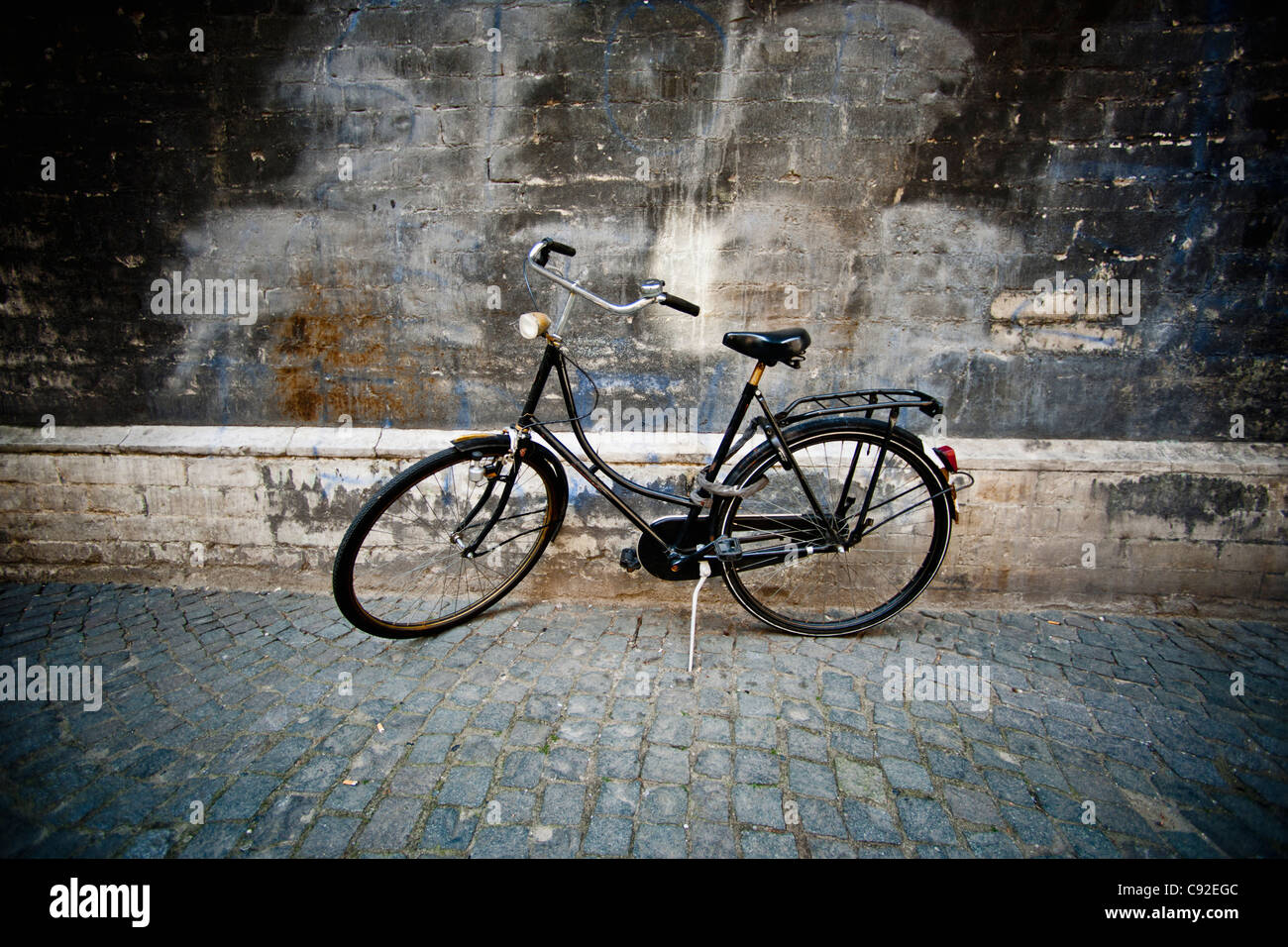 Vintage bicycle parked on cobbled street - Stock Image