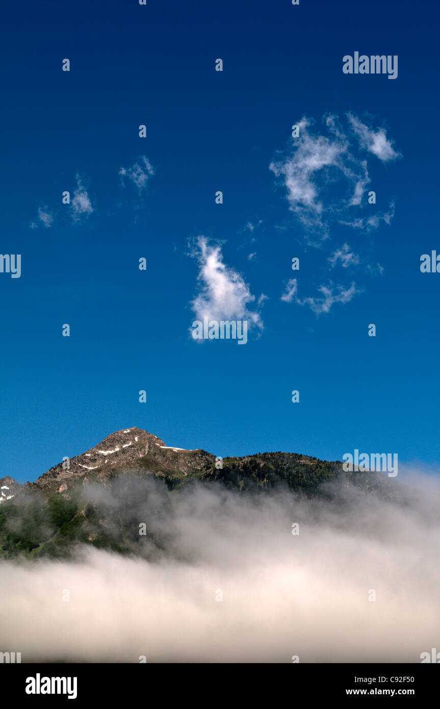 View of mountain top seen through thinning cloud above town of Luz-Saint-Sauveur, Park National des Pyrenees, The - Stock Image