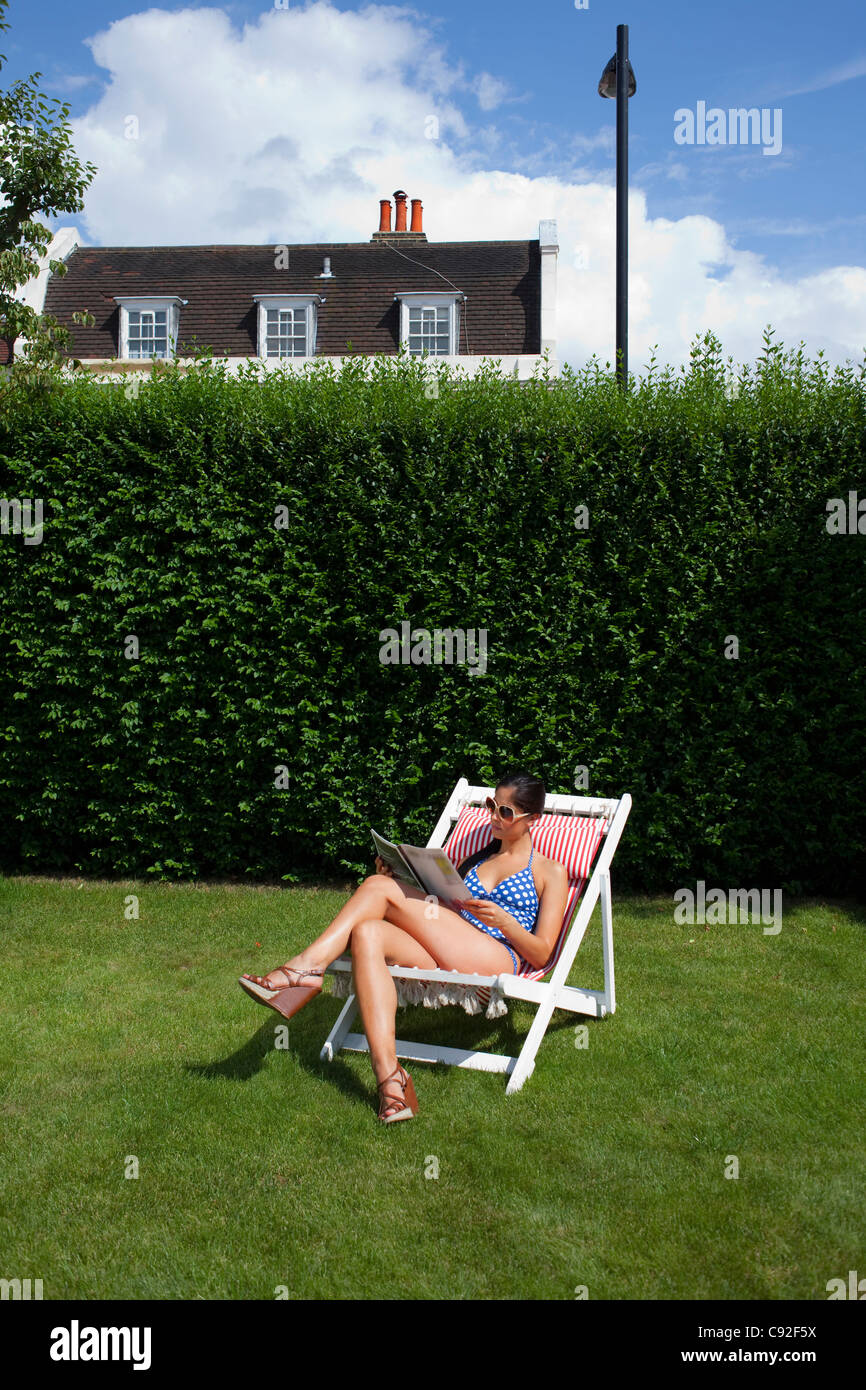 Woman reading and sunbathing - Stock Image