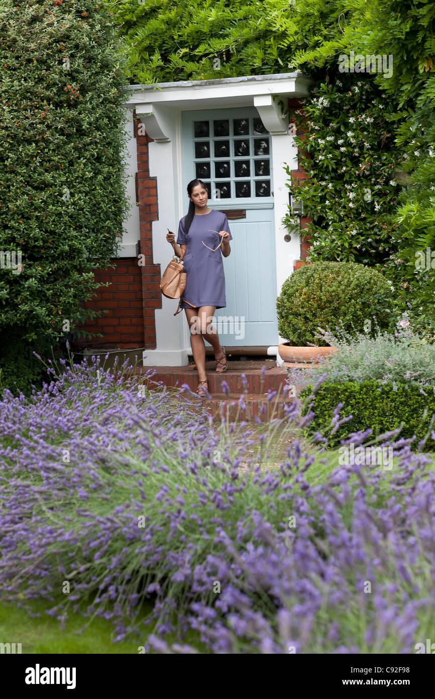 Woman leaving through front door - Stock Image