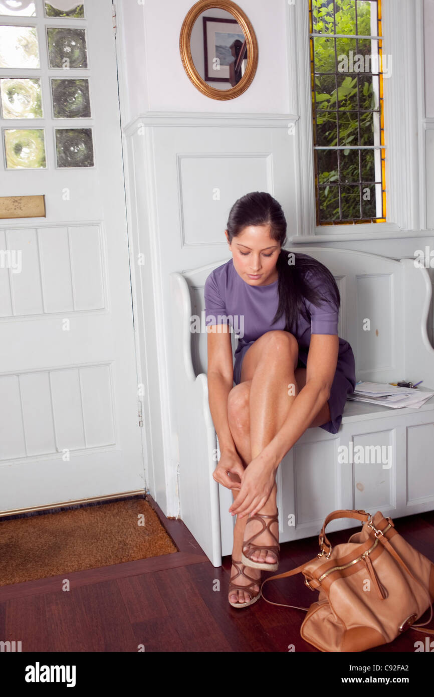 Woman taking off shoes at door - Stock Image