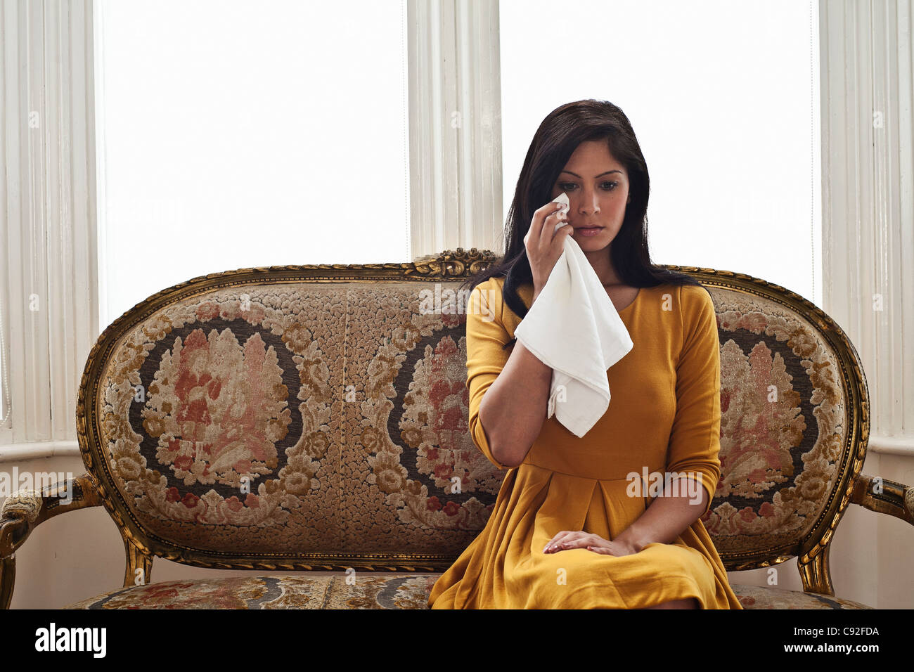 Woman wiping her eyes on sofa - Stock Image