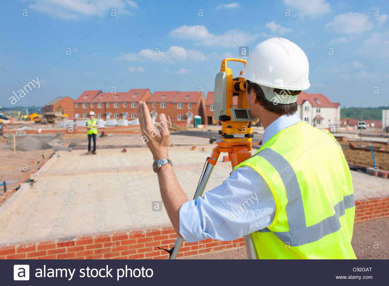 Surveyor behind theodolite gesturing to co-worker at construction site - Stock Image