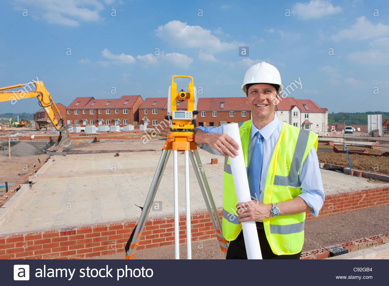 Portrait of smiling surveyor with blueprint leaning on theodolite at construction site - Stock Image