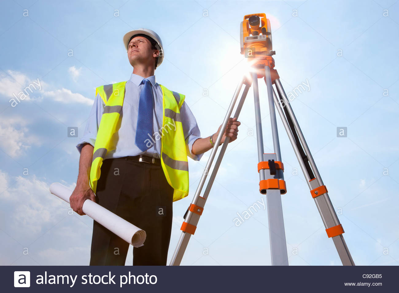 Sun shining behind surveyor with blueprint and theodolite - Stock Image