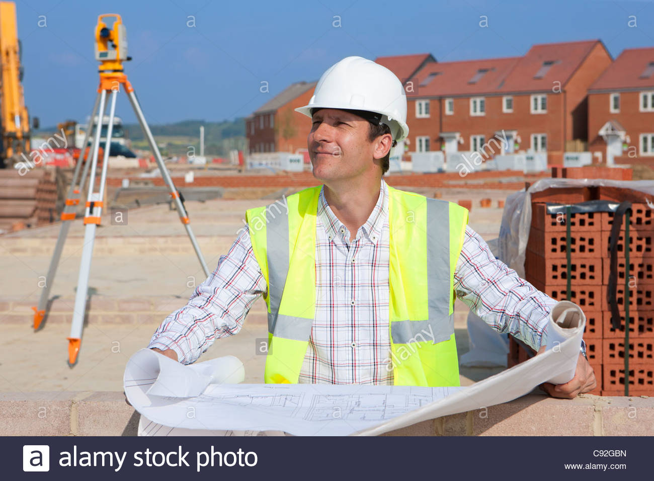 Architect with blueprints at construction site - Stock Image