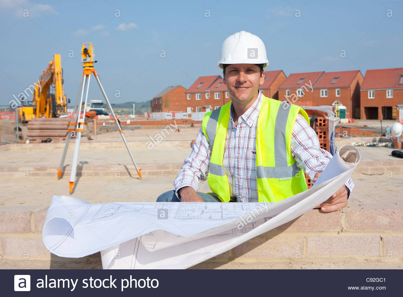 Portrait of smiling architect with blueprints at construction site - Stock Image
