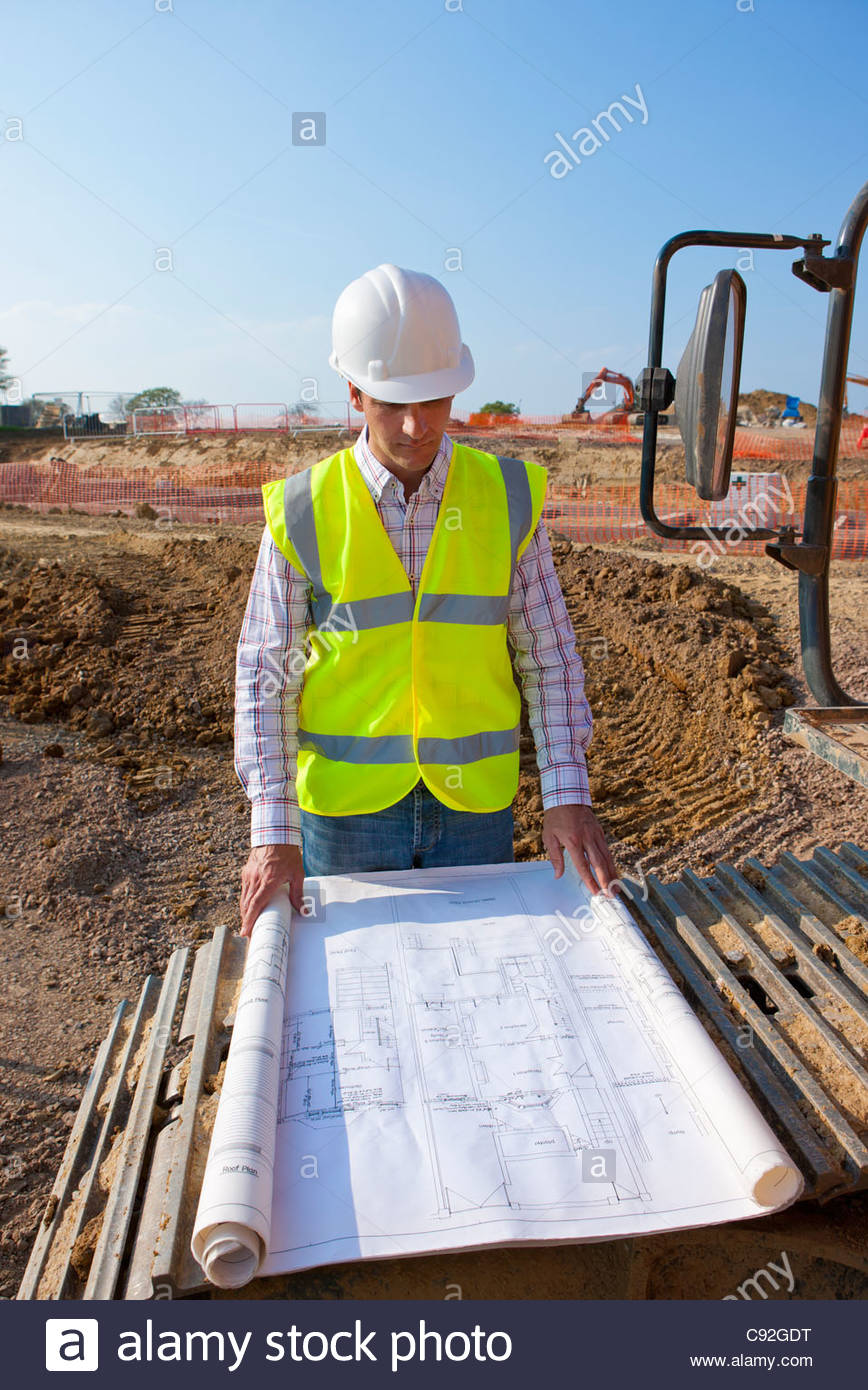 Architect reviewing blueprints at construction site - Stock Image