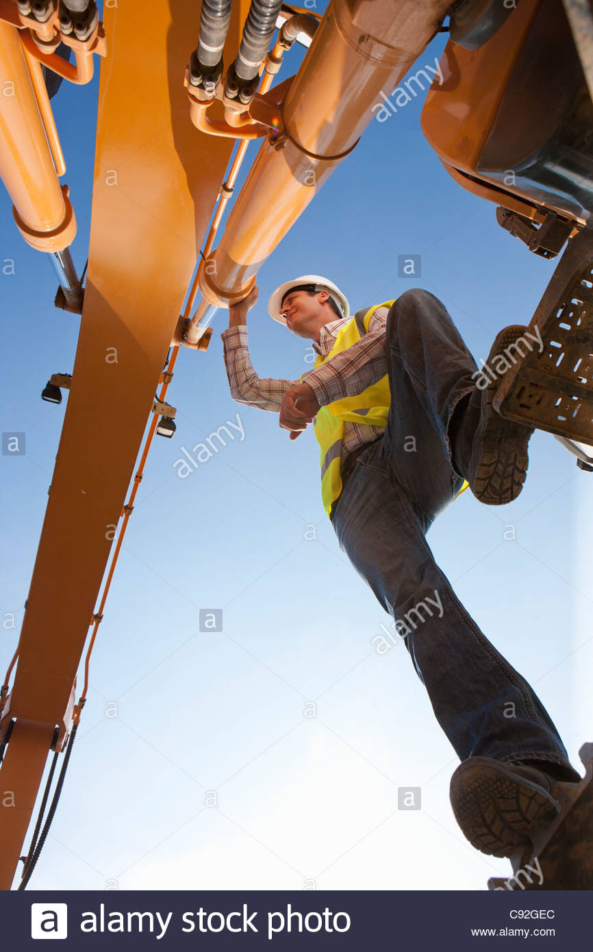 Construction worker leaning on machinery - Stock Image