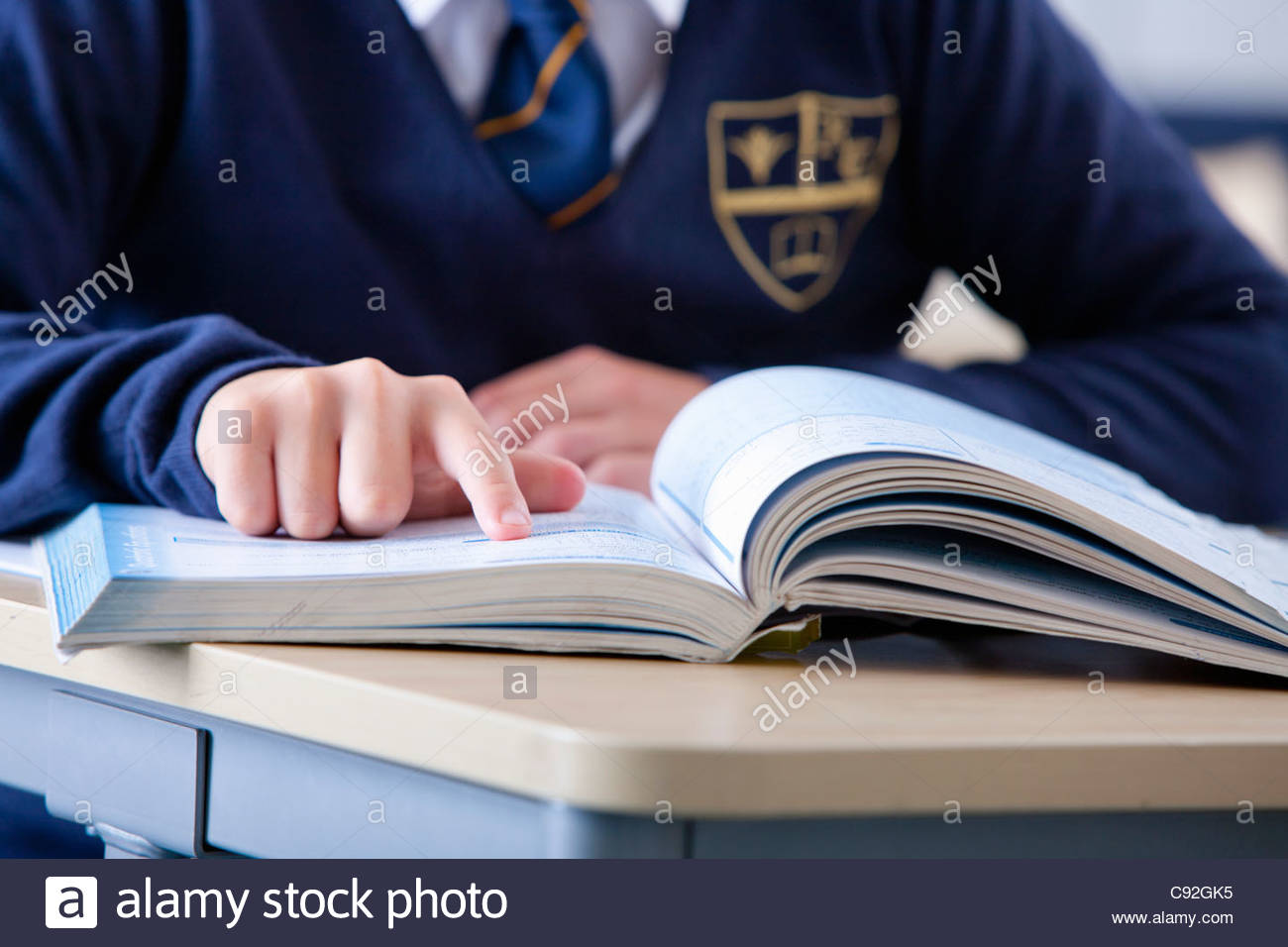 Close up of male student in school uniform pointing to page on book at desk in classroom - Stock Image