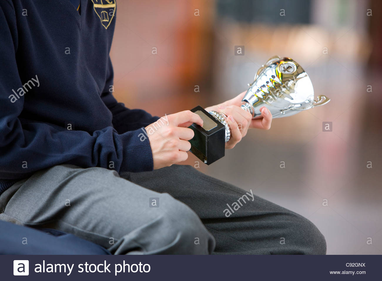 Close up of male student in school uniform holding trophy - Stock Image