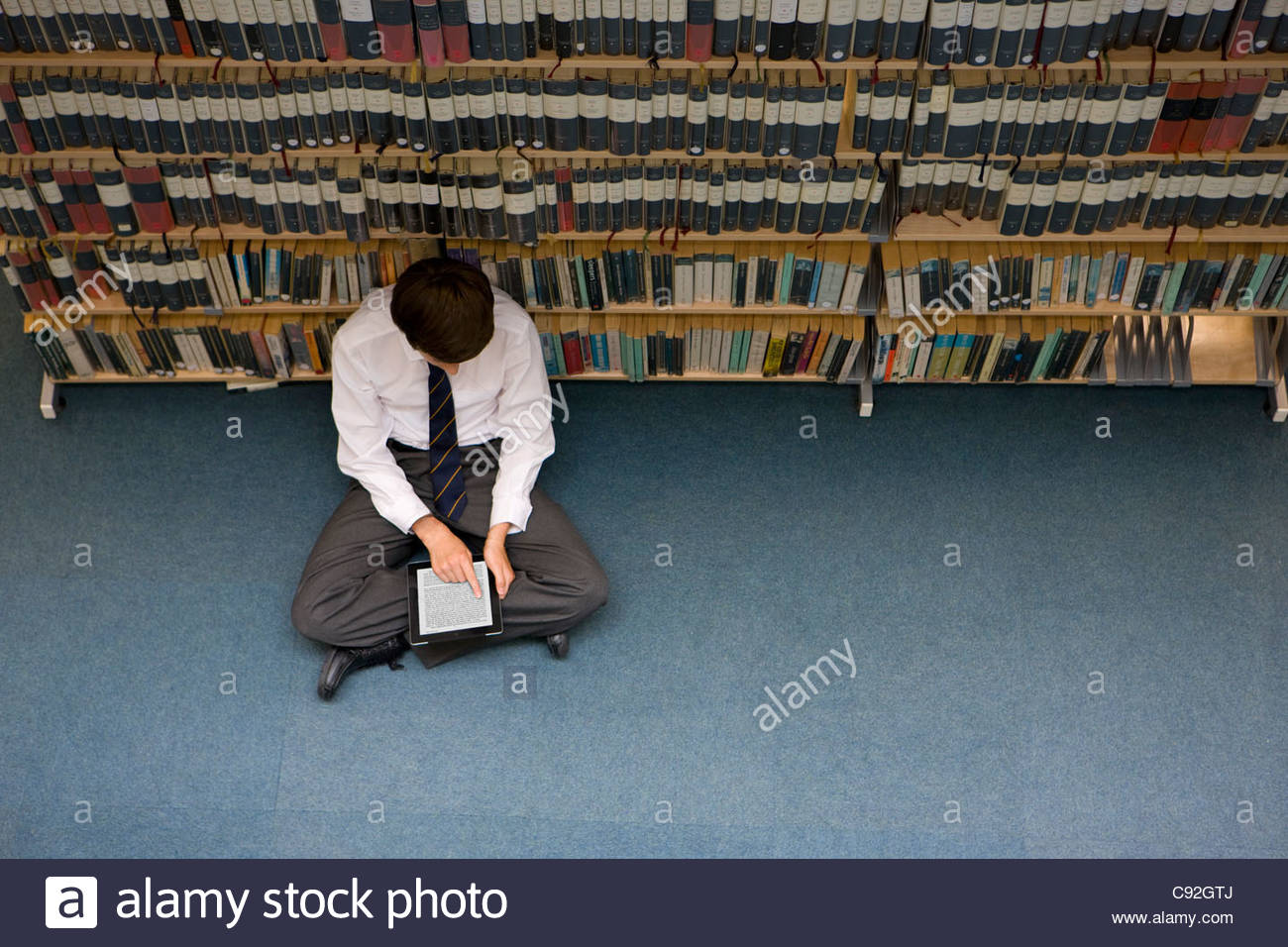 Male student reading electronic book on digital tablet in library - Stock Image