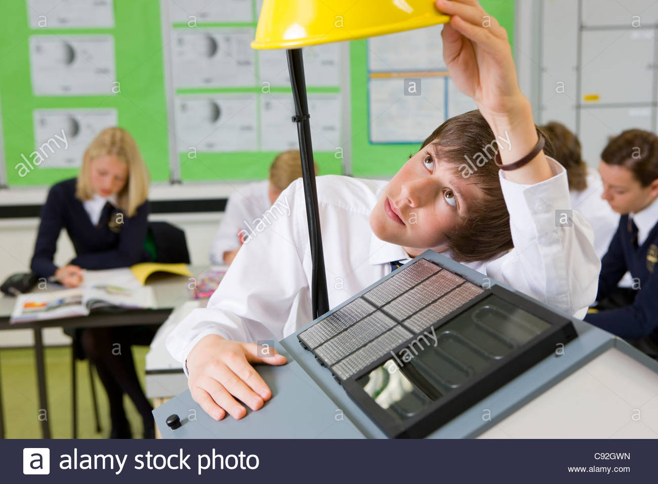 Student experimenting with solar panel and light in science class - Stock Image