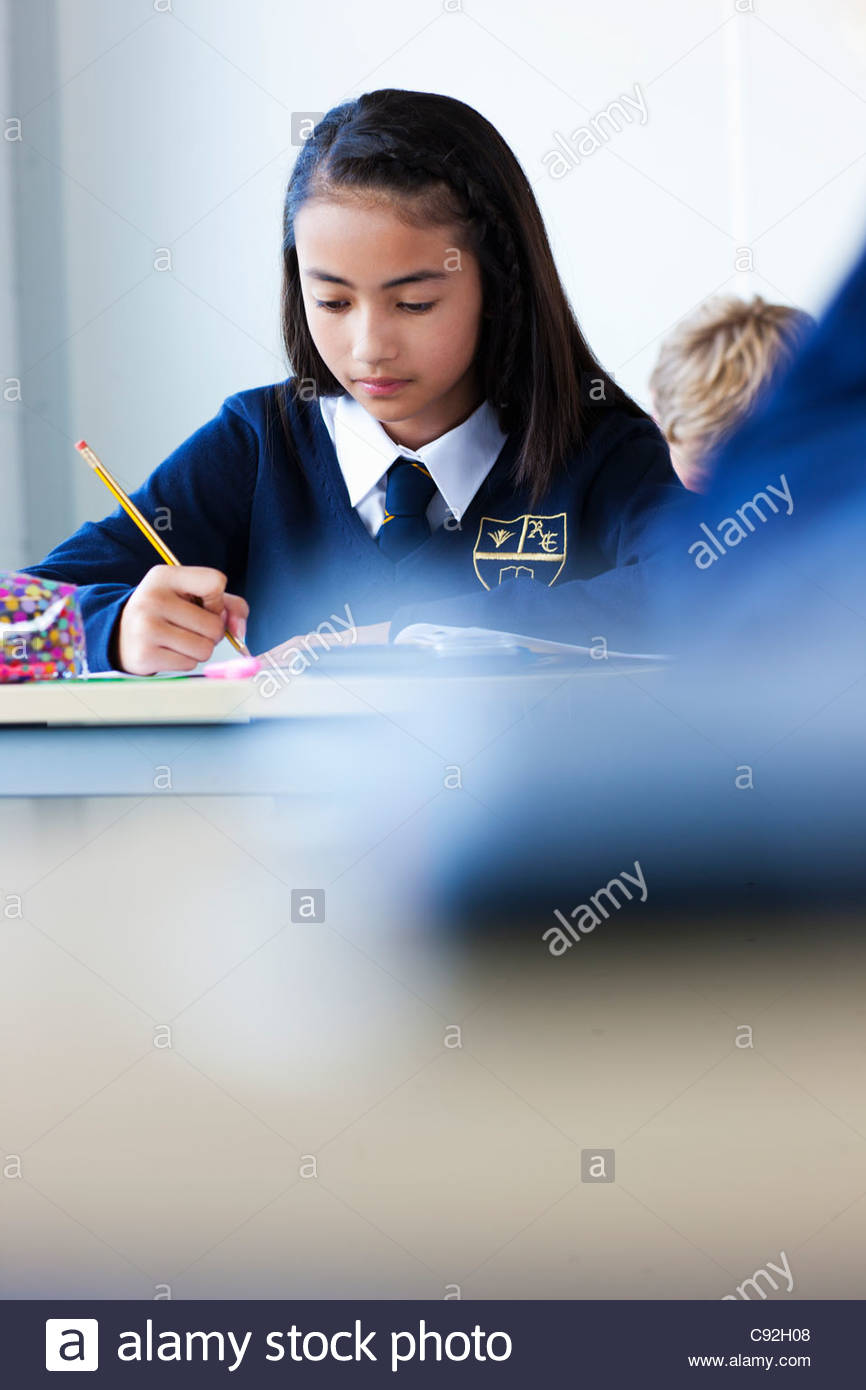 Female student in school uniform taking exam at desk in classroom - Stock Image