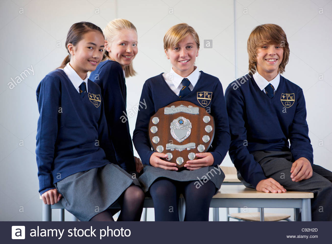 Portrait of smiling students in school uniforms holding award plaque - Stock Image