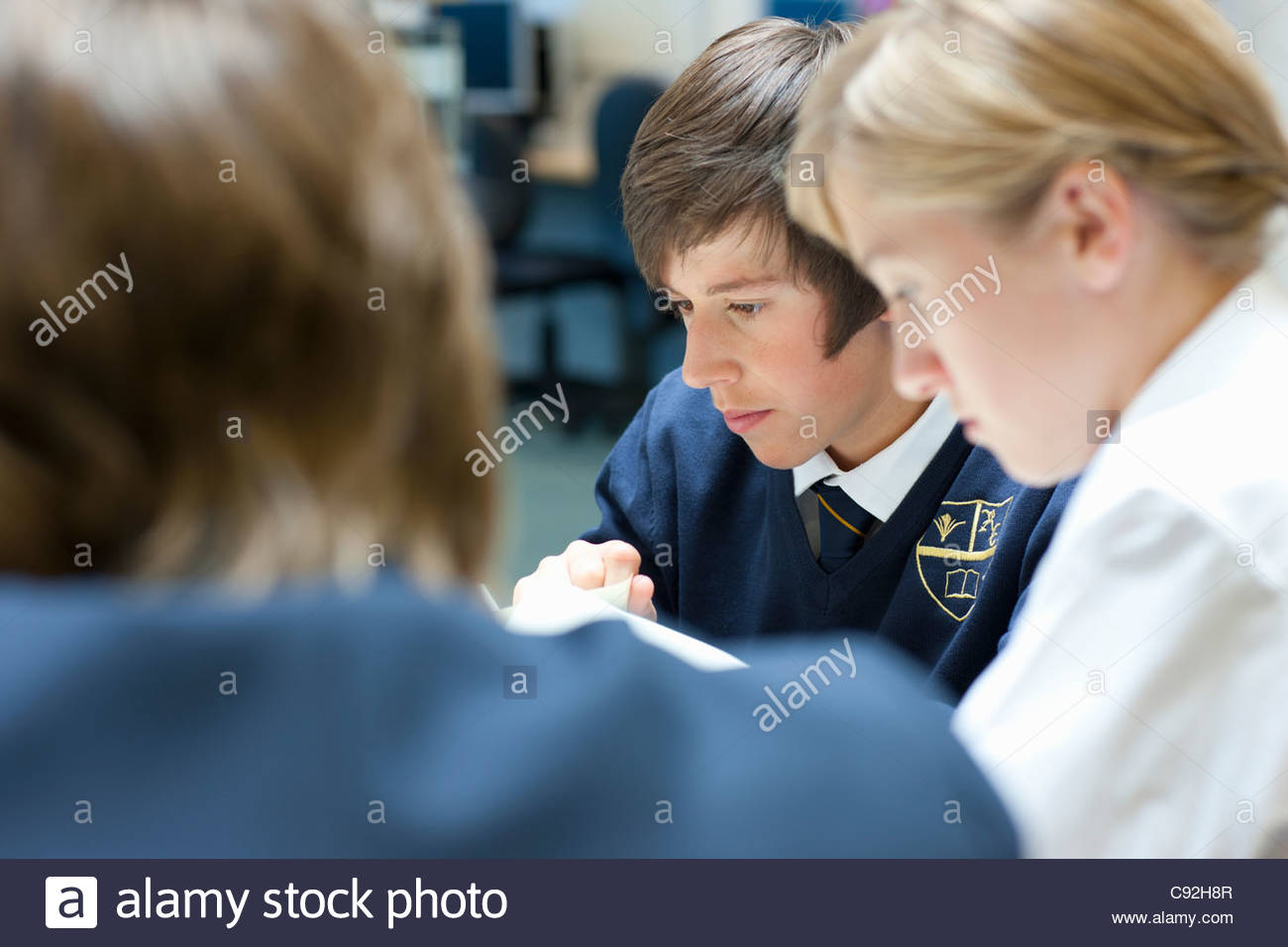 Close up of students in school uniforms studying - Stock Image