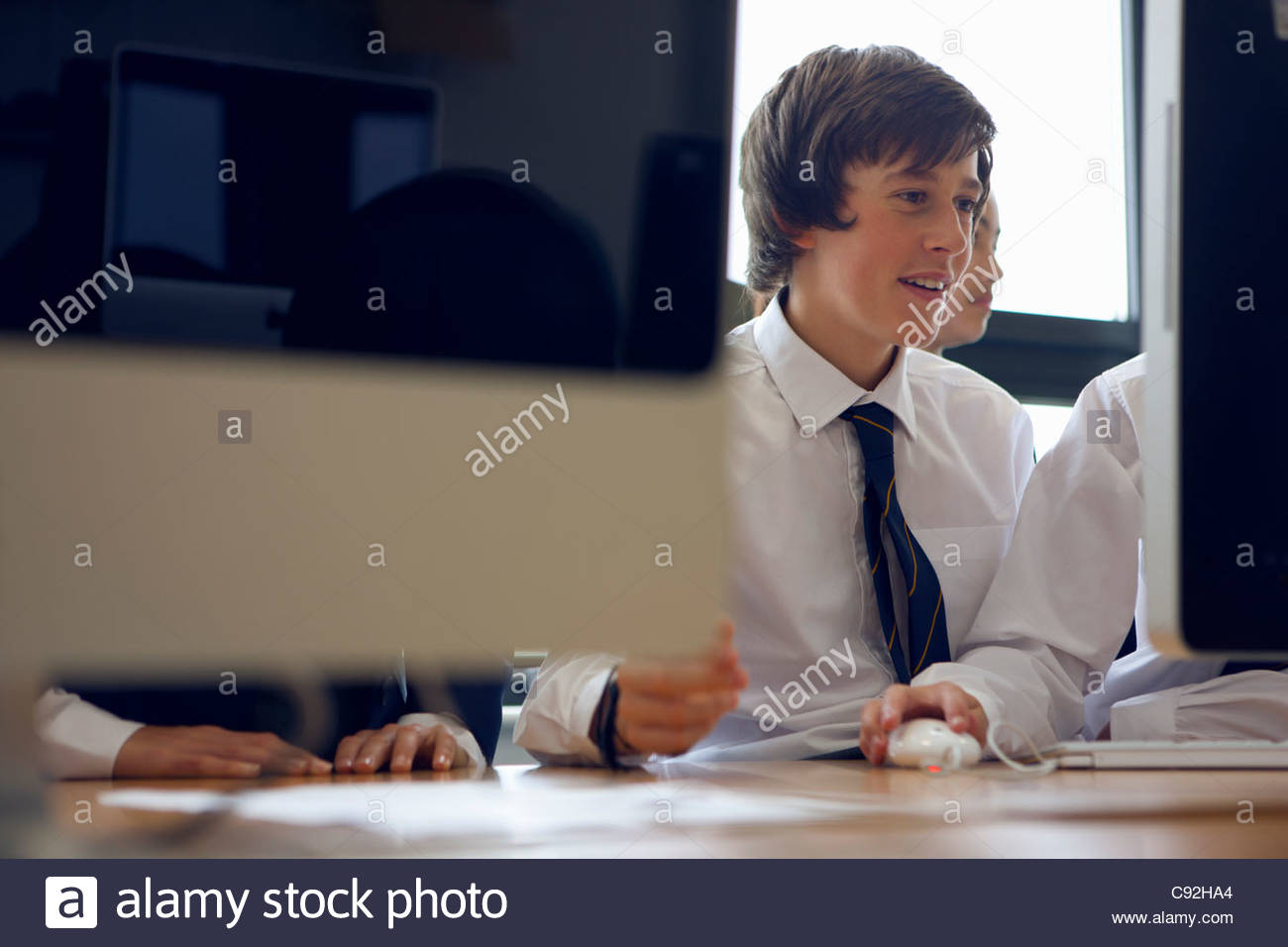 Students in school uniform using computers - Stock Image
