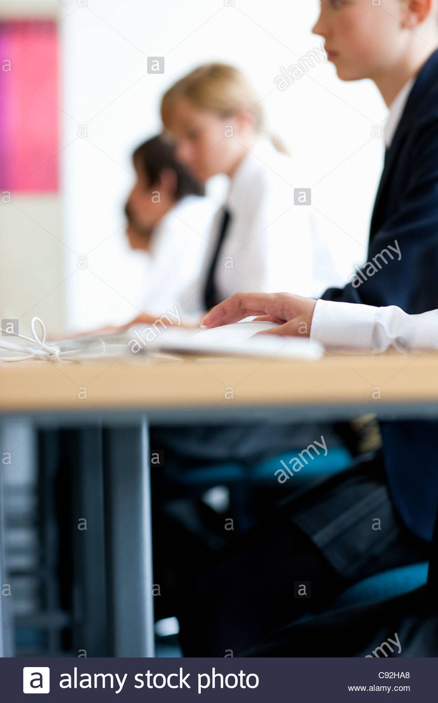 Students in school uniforms sitting at computers - Stock Image