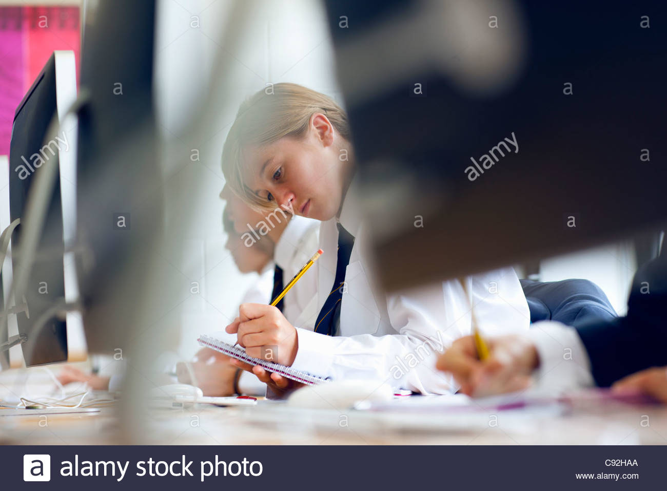 Female student in school uniform writing in notebook at computer - Stock Image