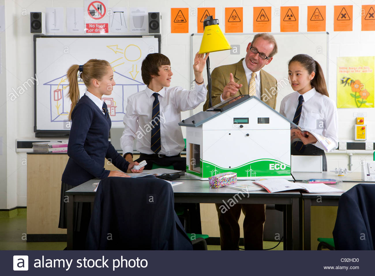 Teacher and students in school uniforms adjusting lamp over solar panels on house model in science class - Stock Image