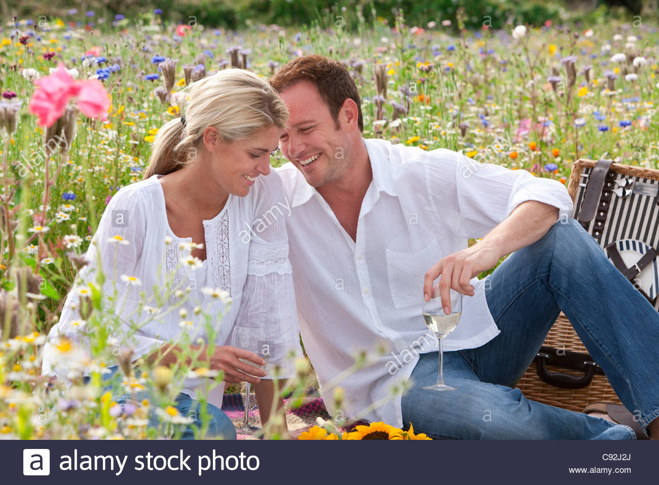 Smiling couple drinking white wine and picnicking in sunny wildflower field - Stock Image