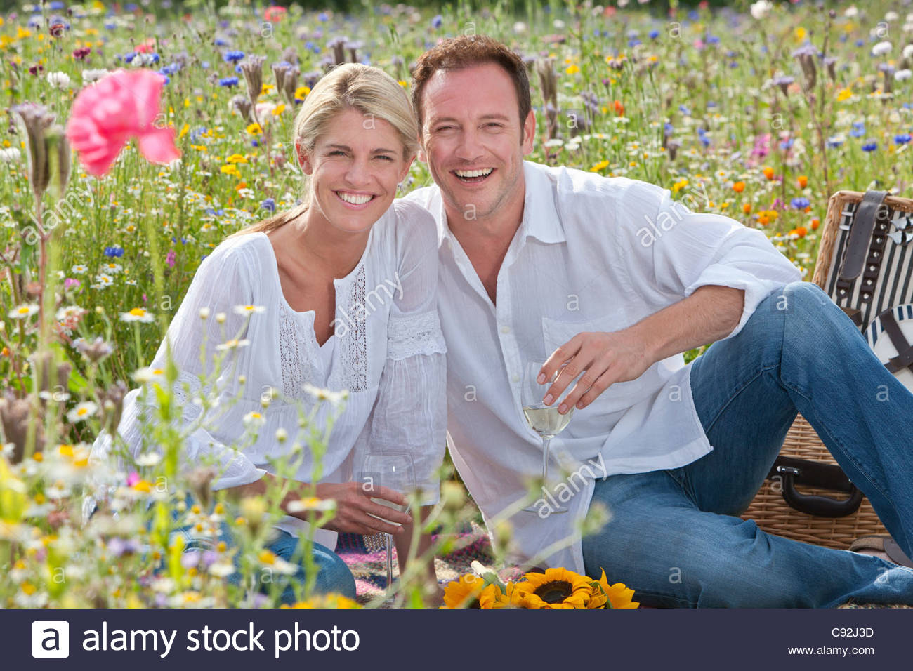 Portrait of smiling couple drinking white wine and picnicking in sunny wildflower field - Stock Image