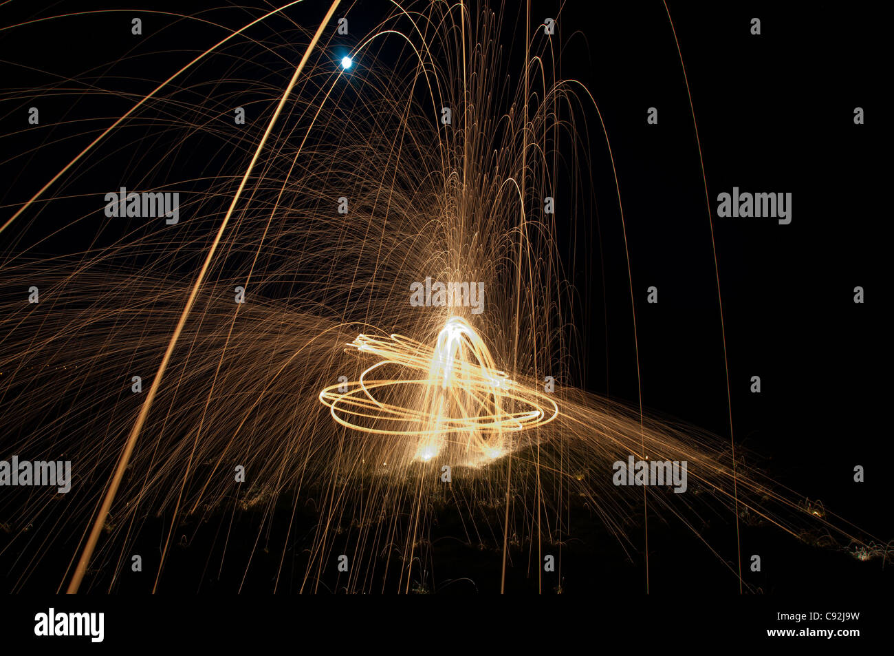 Steel wool spinning, creating gorgeous circular streaks of golden light from burning wire wool inside a whisk attached to wire, or rope. Stock Photo