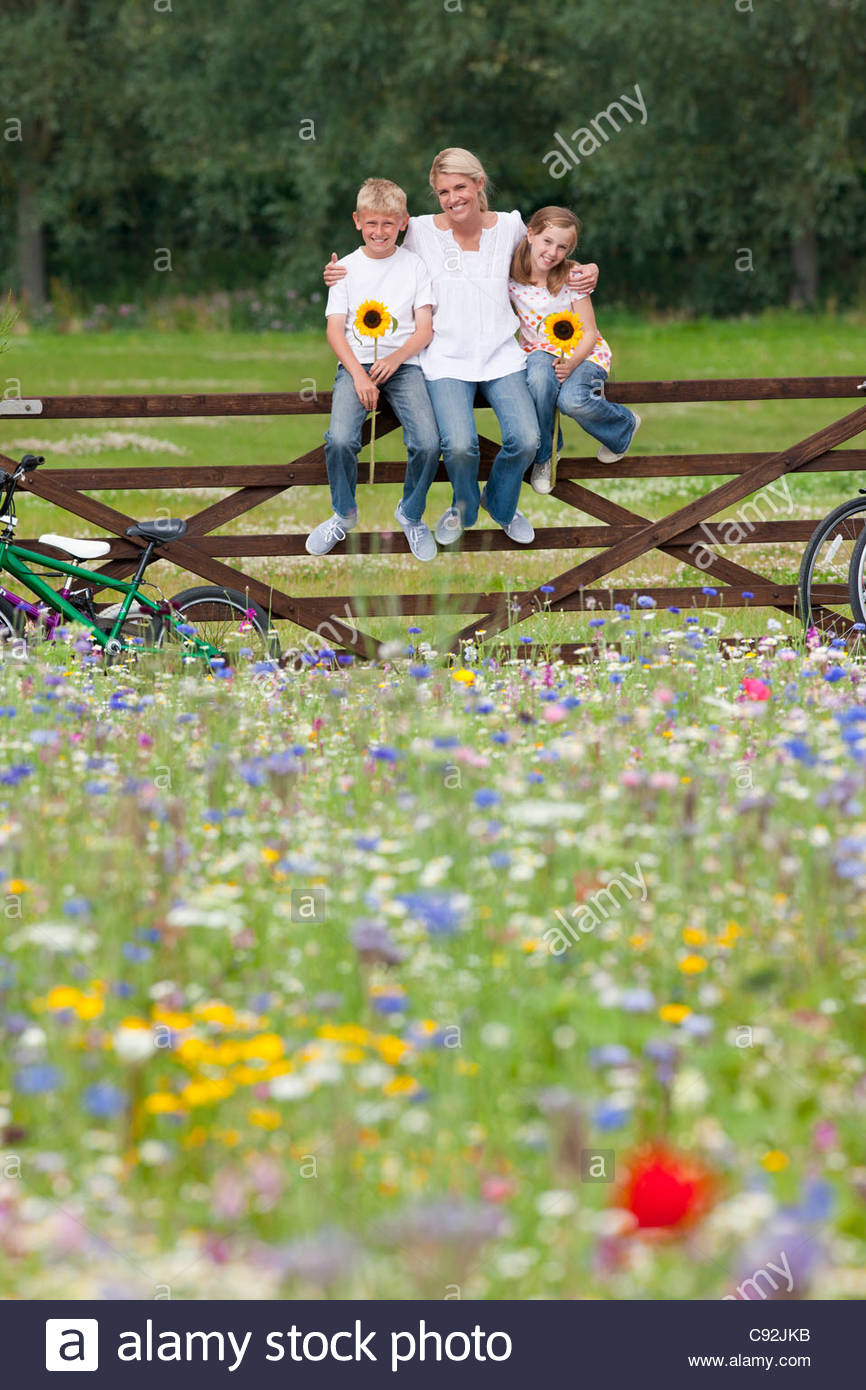 Portrait of smiling family holding sunflowers on fence in wildflower field Stock Photo
