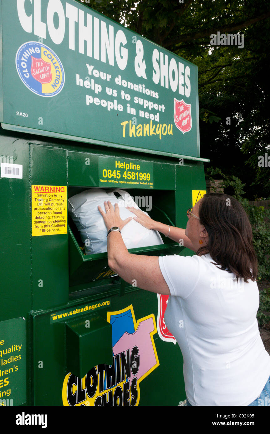 A woman puts a bag of clothing in a Salvation Army charity collection point for unwanted clothing & shoes. - Stock Image
