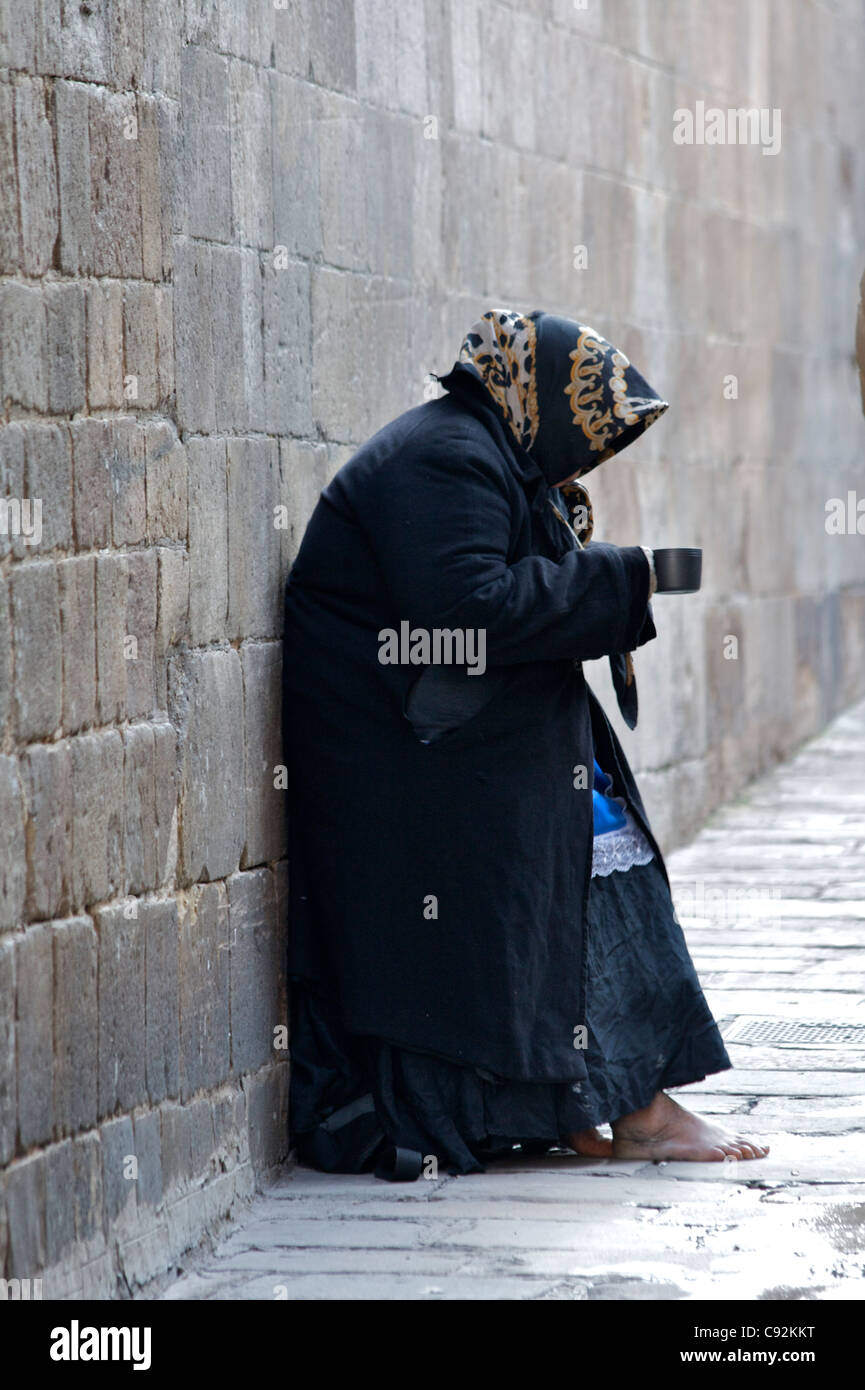 Outside the cathedral Le Seu in Carrer del Bisbe. Beggar. Barcelona, Spain. - Stock Image