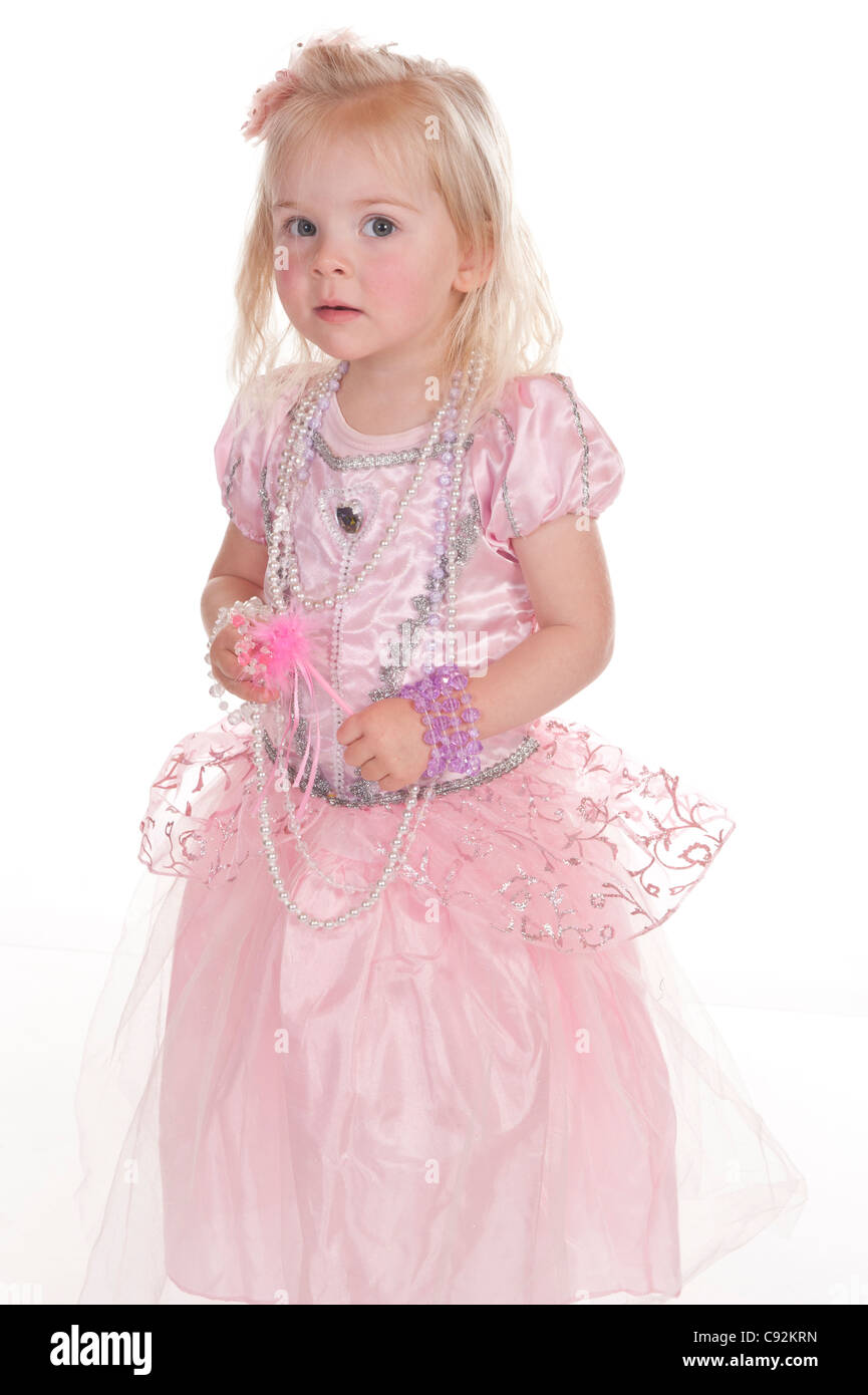 little girl in pink fairy dress tentatively looking at camera against white background - Stock Image