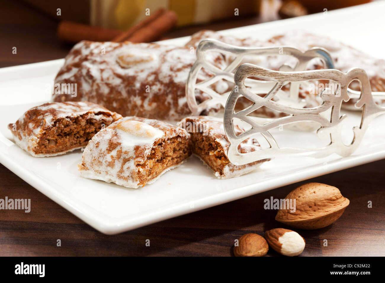Traditional christmas gingerbread cookies from Nuremberg on a plate with silver pastry tongs - Stock Image