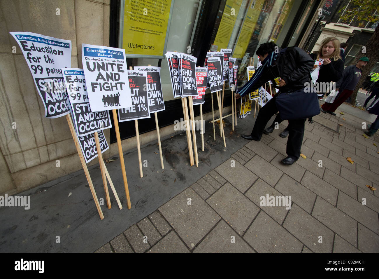 protestors take placards, during students protest in central London UK, about cuts to public spending and increase - Stock Image