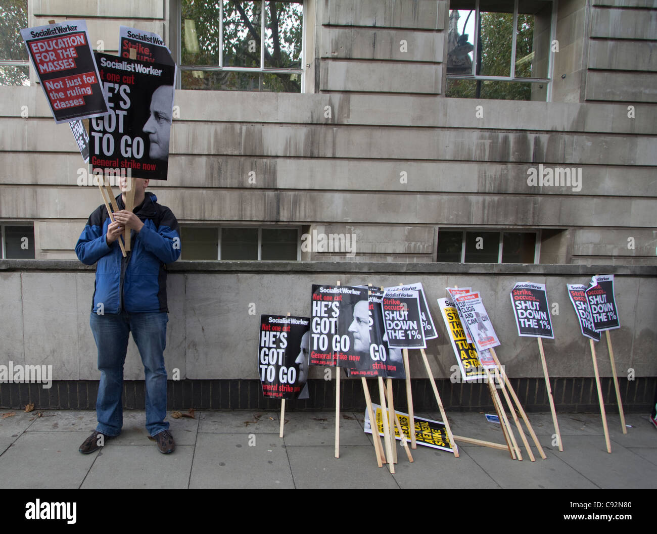 man with placards during students protest in central London UK, about cuts to public spending and increase in tuition - Stock Image