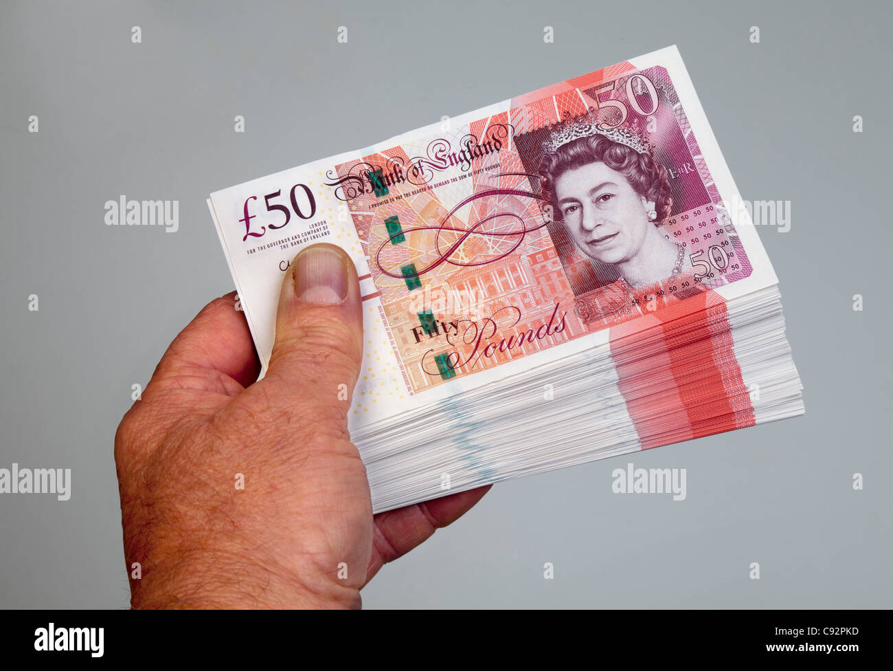 50 pound British currency bank notes £50 cash held in male hand - Stock Image