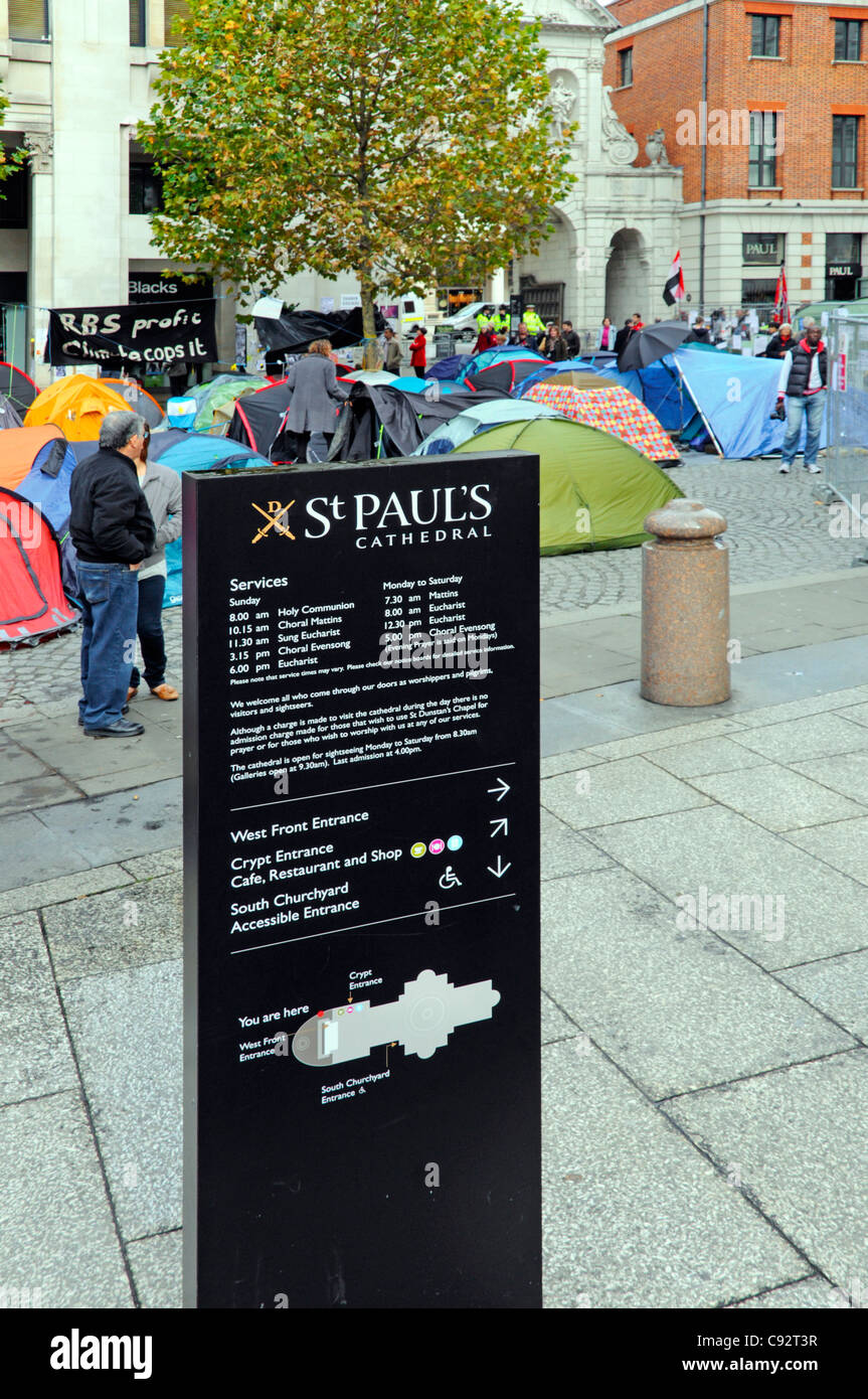 St Pauls cathedral information panel with anti capitalist protesters tents and spectators Stock Exchange entrance - Stock Image