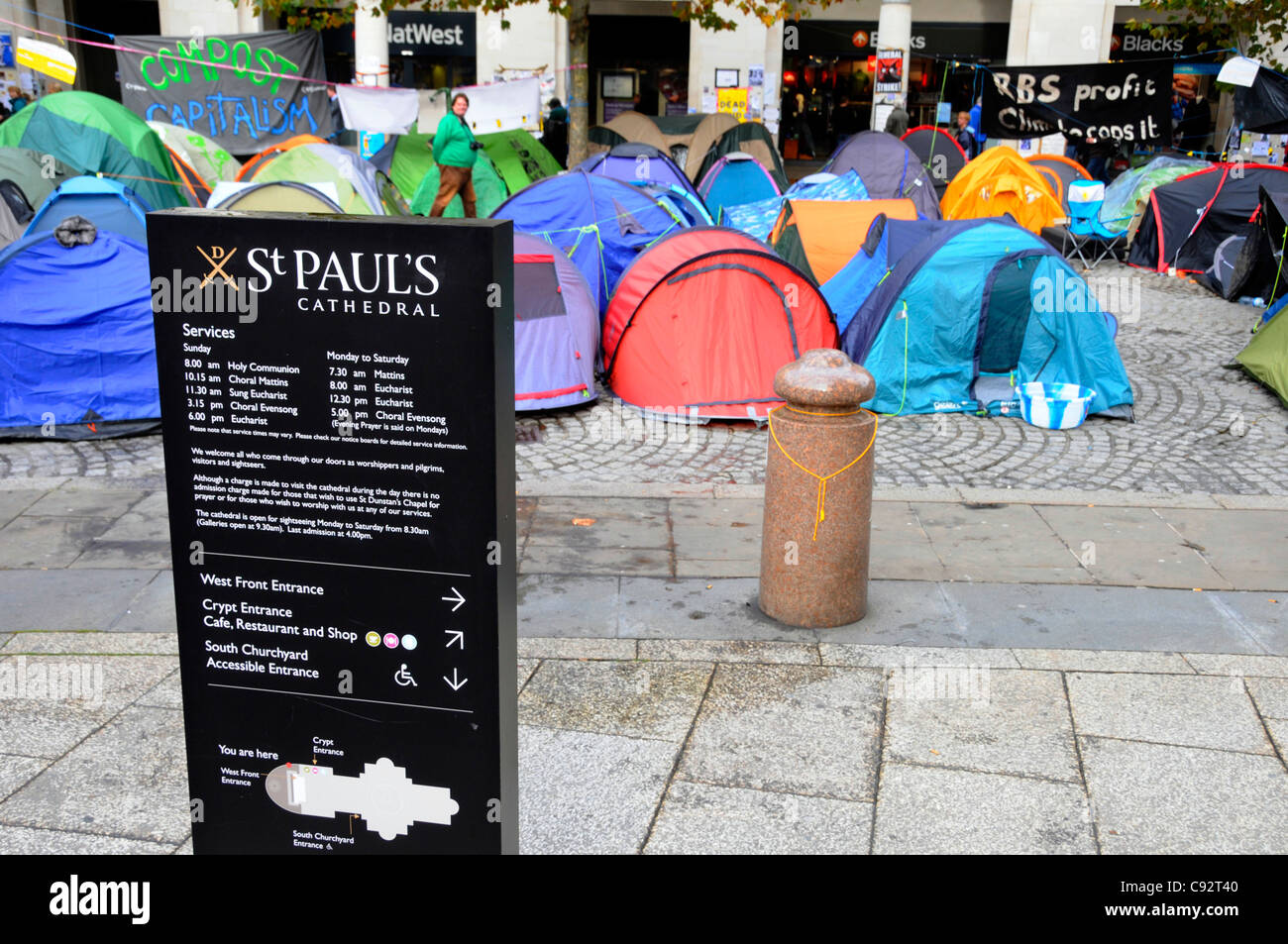 St Pauls cathedral information panel with anti capitalist protesters tents and Stock Exchange entrance beyond City - Stock Image