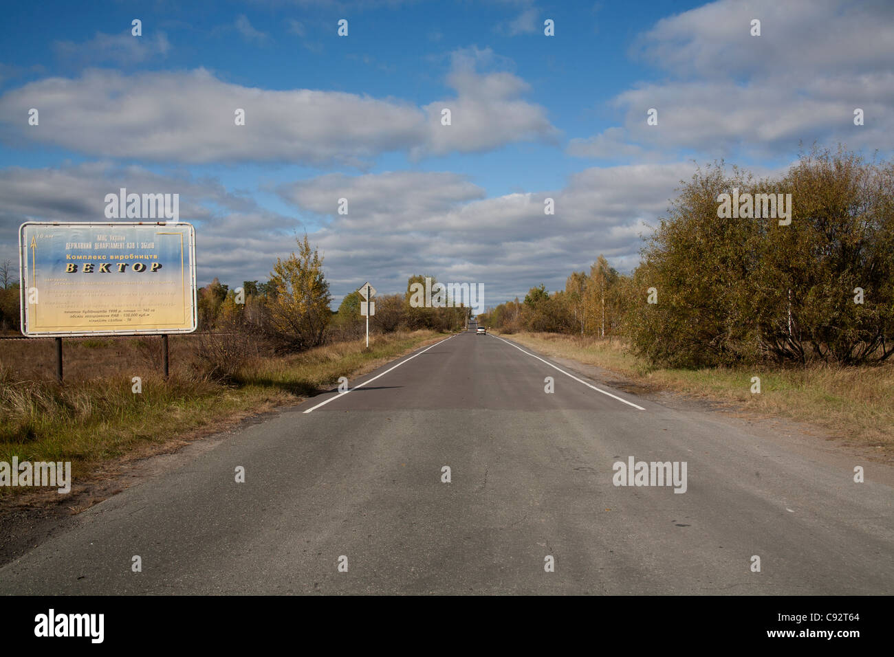 Empty road with weathered sign in the 10 km exclusion zone Chernobyl Ukraine - Stock Image