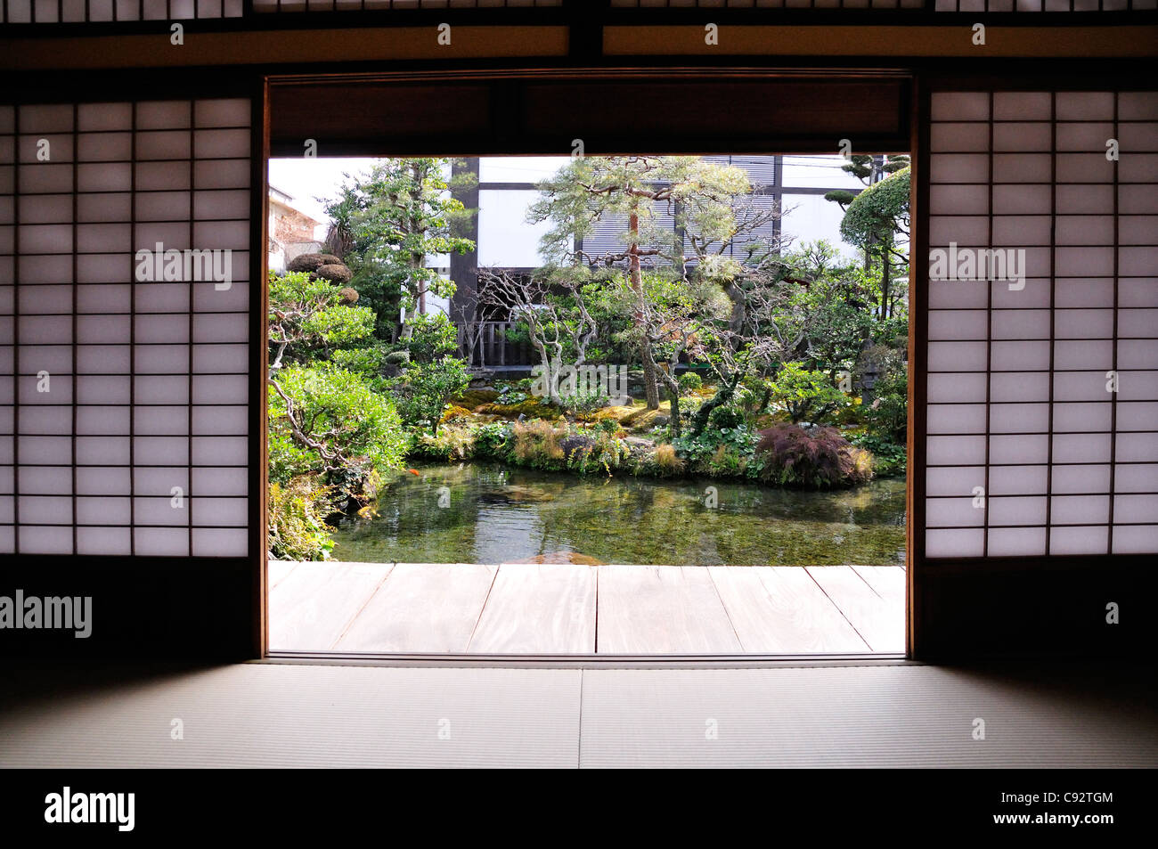 A traditional Japanese house and garden with carp swimming in pond. - Stock Image