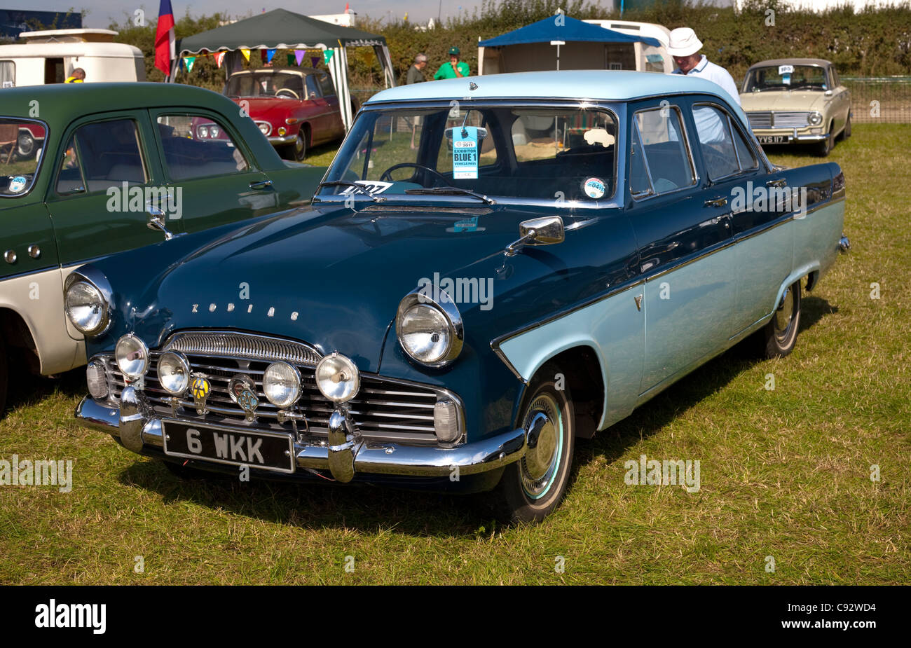 two tone blue ford zodiac with other classic cars at a show with people walking and admiring - Stock Image
