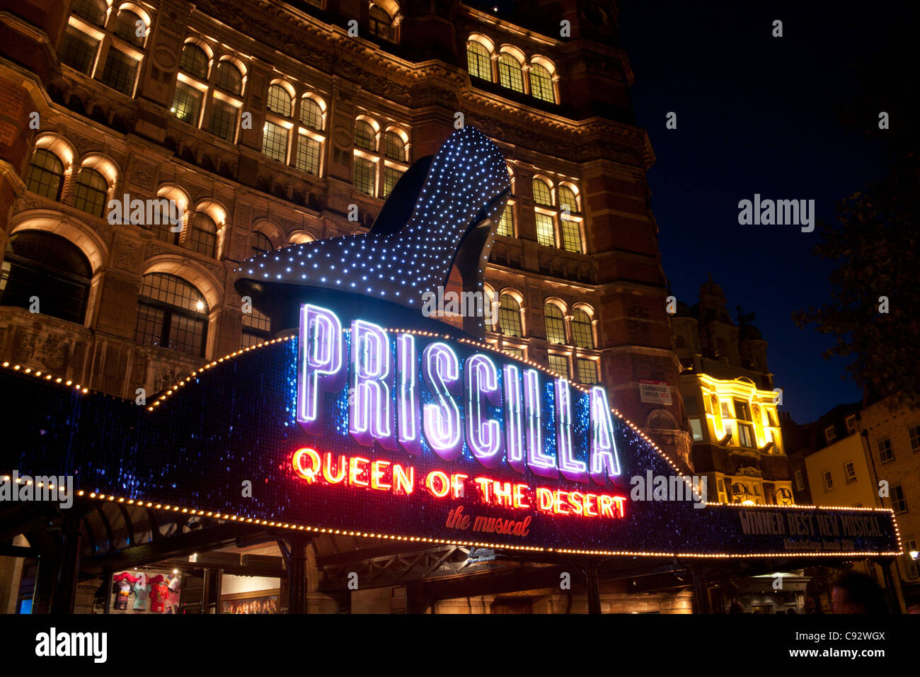 Palace Theatre at night with high heeled shoe and neon sign advertising Priscilla Queen of the Desert musical London - Stock Image