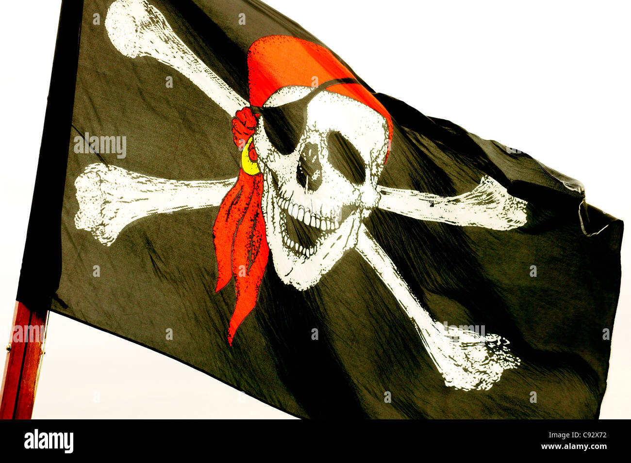 The Jolly Roger skull and cross bones pirate flag - Stock Image