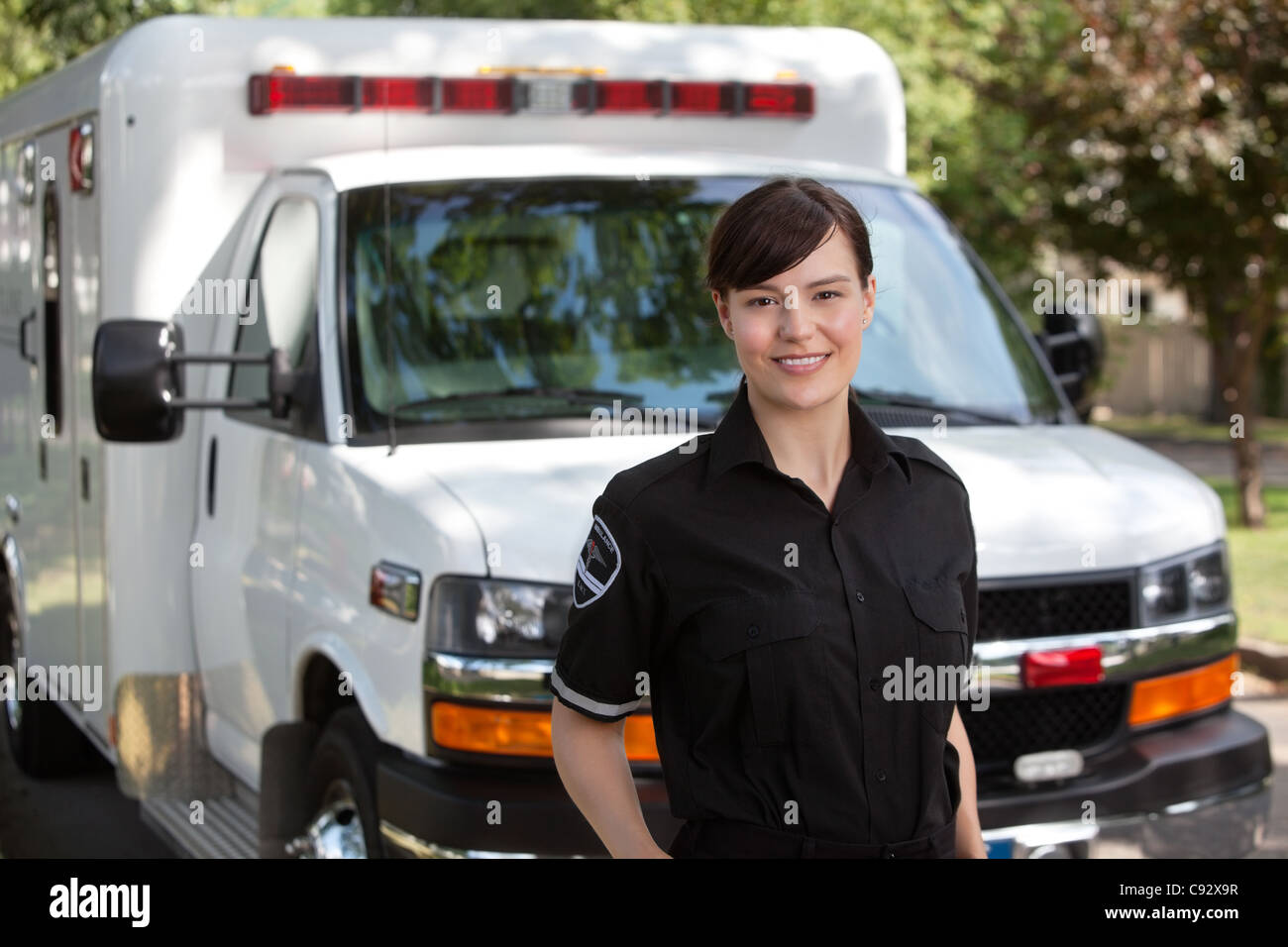 Portrait of attractive paramedic standing in front of ambulance - Stock Image