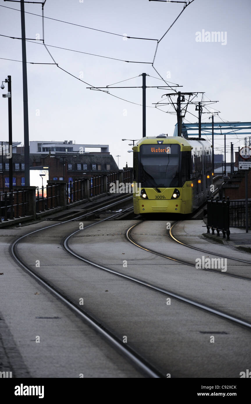 Yellow Metrolink tram crossing Oxford Rd bridge, Manchester - Stock Image