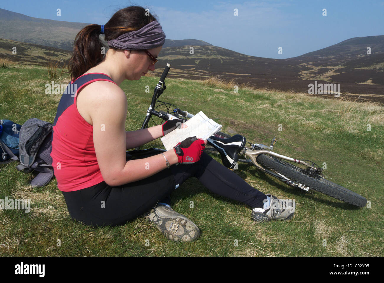 A lady mountain biker looking at a map - Stock Image